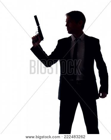 Silhouette of gangster in business suit with gun at hand