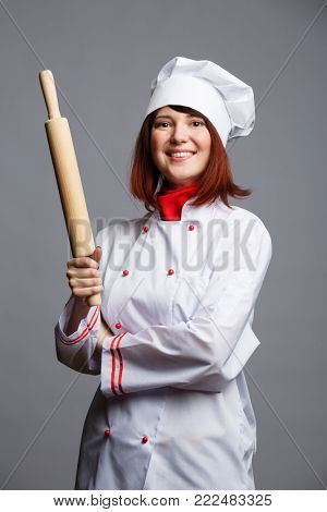 Image of brunette cook in white coat and cap with rolling pin in hands