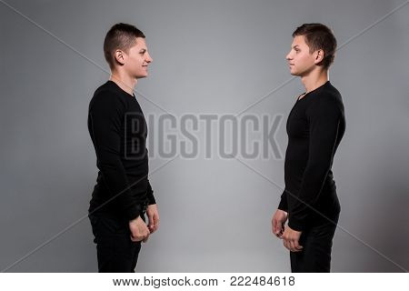 Portrait of young twin brothers standing face to face on gray background. Copy space. Casual twin brothers.