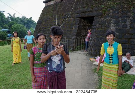 Mrauk-u, Rakhine State / Myanmar - October 18 2016: Traditionally dressed up teenagers and a young man with a mobile phone in contrast to an old beggar in front of an ancient temple