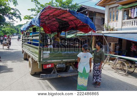 Mrauk-u, Rakhine State / Myanmar - October 18 2016: Women waiting at a pickup truck in the middle of the main road