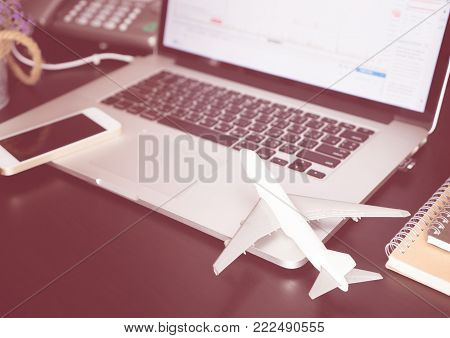Office desk with plane and laptop for business travel concept