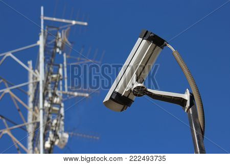 Security surveillance camera watching with satellite equipment in background white with blue sky.