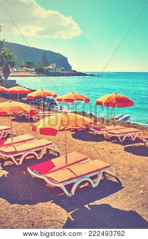 Vacant umbrellas and chaise longues on a sea beach, Tenerife. Retro style filtered image