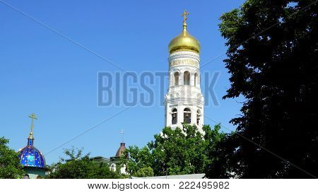 Holy Dormition Monastery Odessa. monastery bell tower. View of the bell tower from behind the trees