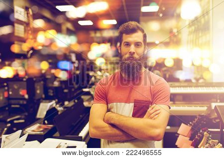 people, musical instruments and small business concept - male assistant or customer with beard at music store over lights