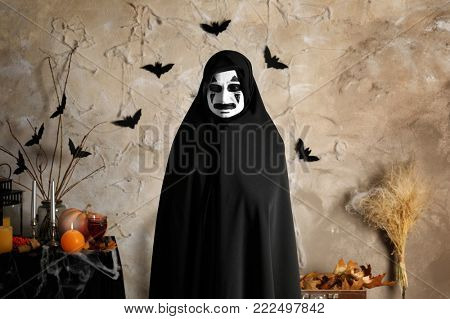 Mystic creature in black cloak on light background