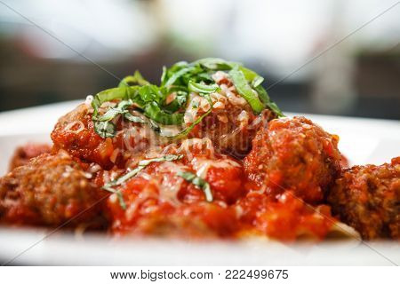 Meatball penne pasta with spicy tomato sauce and herbs