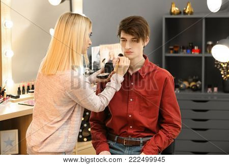 Professional artist creating makeup for male model in room
