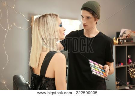 Professional artist creating makeup for beautiful model in room