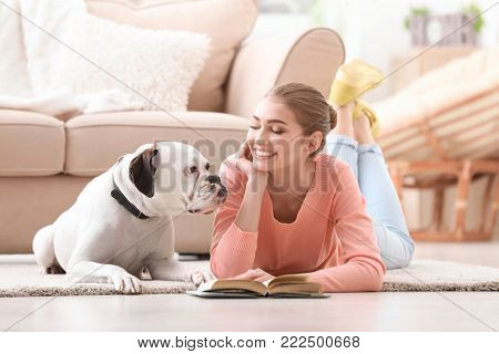 Woman reading book to cute white Boxer dog indoors. Pet adoption