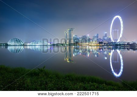 SINGAPORE, 22 OCT 2017: Gardens by the Bay, the Marina Bay Sands hotel and the Flyer Wheel appear at night across the bay, in Singapore.