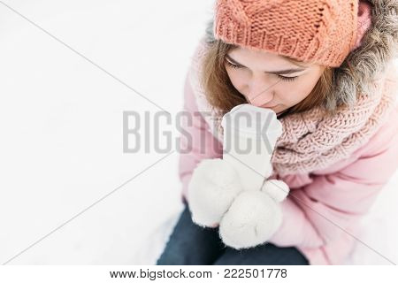 Portrait Of A Beautiful Young Girl In White Knitted Mittens, Outdoors, Drinking A Hot Beverage , Bri