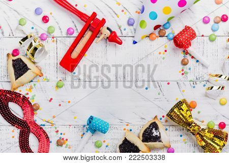 Festive party, carnival or Purim holiday background. Bright hats, masks and confetti on yellow background. Copy space