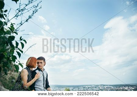 couple sitis on the hill with ponaramic view on a city