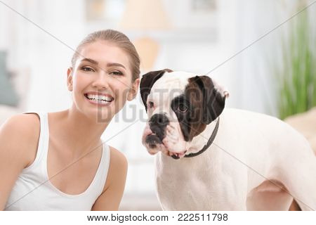 Woman with cute white Boxer dog on blurred background. Pet adoption