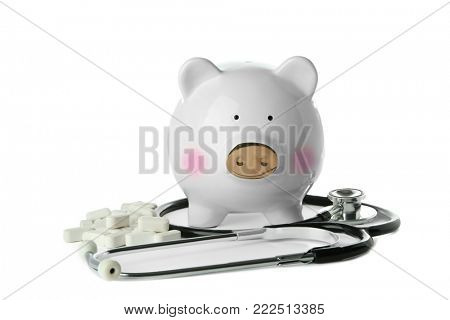 Piggy bank with stethoscope and pills on white background. Health care concept