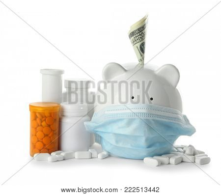 Piggy bank in medical mask with banknote and pills on white background. Health care concept