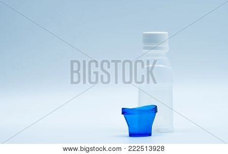 Sterile eye lotion in white plastic bottle with blue eyebath and copy space and blank label. Eye wash after contact pollution environment or after swimming in chlorine contaminate pool.