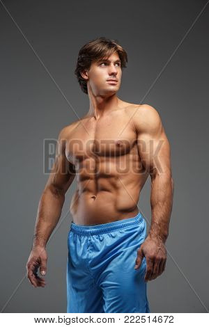 Shirtles muscular man in blue shorts showing his muscles over grey background.