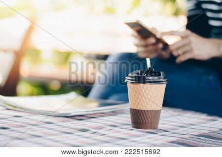 Hot Coffee cup on table with blurred image background of woman use smart phone, selective focus.
