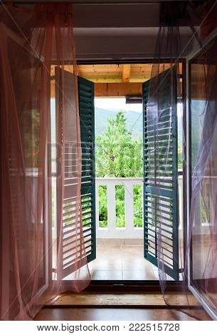 Semi-open green wooden shutters on balcony window and spectacular view of the summer mountains. Look from inside to outside. Colored inspiring vertical image.