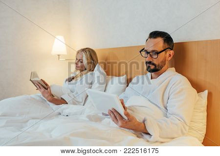 mid adult couple in bathrobes reading book and using digital tablet while lying in bed in hotel room