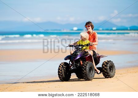 Teenager and his little brother riding quad bike on tropical beach. Active teen age boy on quadricycle. All-terrain vehicle ride. Motor cross sports on ocean sand dune. Kids summer vacation activity.