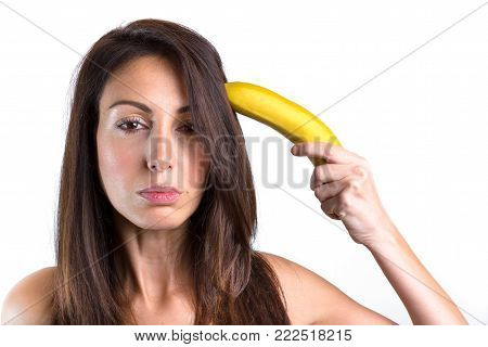 Conceptual portrait of a young woman trying to shoot herself with a banana gun. Space for text.