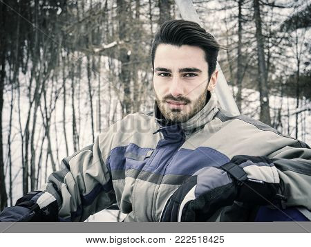 Portrait of handsome man in skiing suit sitting on chairlift rising up and looking at camera.