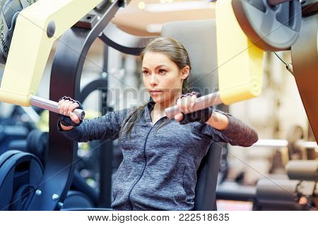 fitness, sport, bodybuilding, exercising and people concept - young woman flexing muscles on seated chest press machine in gym