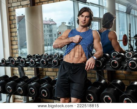 Positive muscular guy in blue t shirt holding dumbells in a gym.