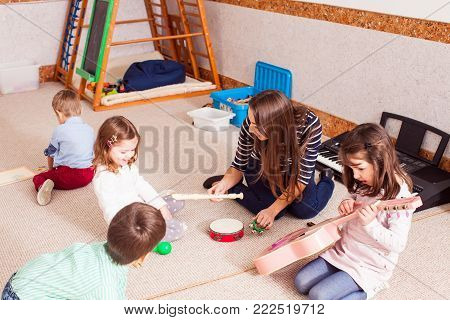 Music making lesson. The young woman teacher plays with children, little orchestra