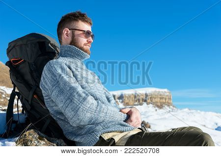 Portrait of a traveler's Hipster in sunglasses and a knitted gray sweater resting against the backdrop of a beautiful winter landscape with a table mountain in the snow. The concept of relaxing in the mountains and trekking with walking tours