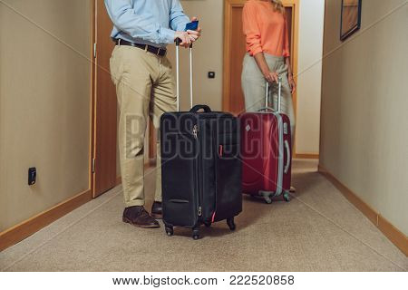 cropped shot of mature couple with suitcases standing in hotel hallway