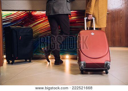 low section of mature couple with suitcases standing at reception in hotel