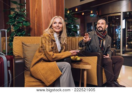 smiling mid adult couple looking away while sitting on hotel hallway