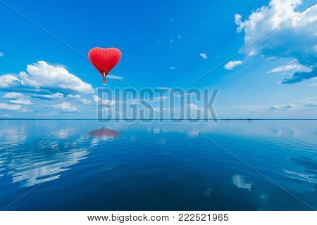Red hot air balloon in the shape of a heart above the lake surface at windless weather time. Present trip on Valentine's Day.