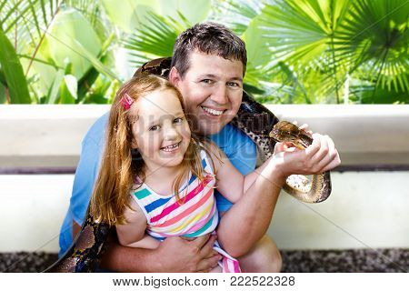 Father And Child Hold And Feed Python Snake At Zoo