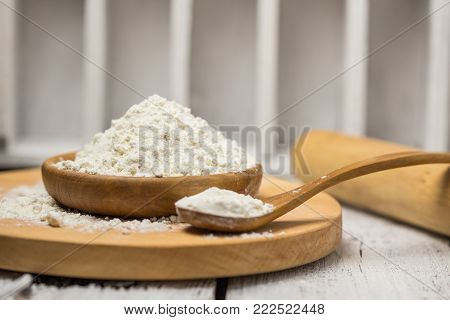 Fine White Flour In Dark Wooden Bowl Isolated On White  Wood From Above. Spilled Flour.
