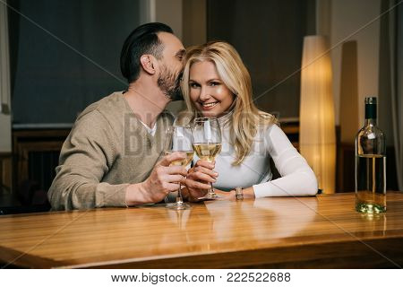 handsome mature man whispering something to smiling woman while drinking wine in hotel restaurant