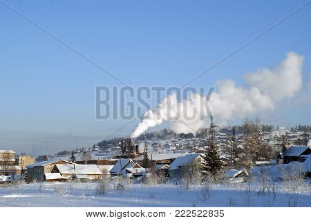 Winter view of the Urals village with a working obsolete metallurgical plant in the middle of it