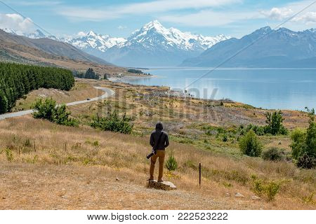Young male photographer in hoody watching at Mount Cook, one of the most famous snowy mountain at peter's lookout in South Island, New Zealand. Travel in summer concept