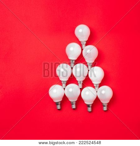 The christmas tree from lantern lamps laying on red background with copy space. Christmas ceativity decorations.