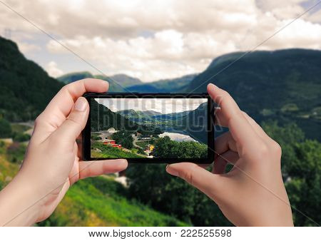 Picture of villagei in Norway on mobile phone. Female take picture houses and port in Lysefjorden on smart phone