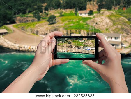 Picture of village Songesand in Norway on mobile phone. Female take picture houses and port in Lysefjorden on smart phone
