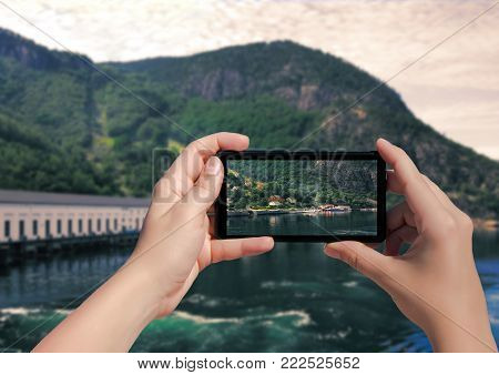 Picture of village Florli in Norway on mobile phone. Female take picture houses and port in Lysefjorden on smart phone.