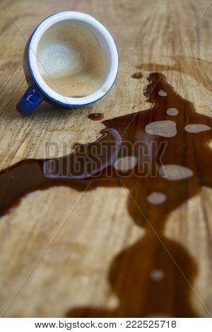 cup of espresso coffee spilt on a wooden table