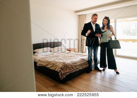 Male real estate agent showing apartment and discussing the contract and documents with a female customer. Realtor showing the contract papers to female client while standing inside the bedroom of a new house.