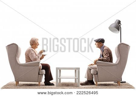 Elderly woman with a cup and an elderly man sitting in armchairs and having a conversation isolated on white background